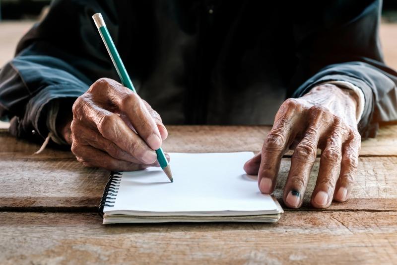 葬儀について事前にエンディングノートを書いている男性